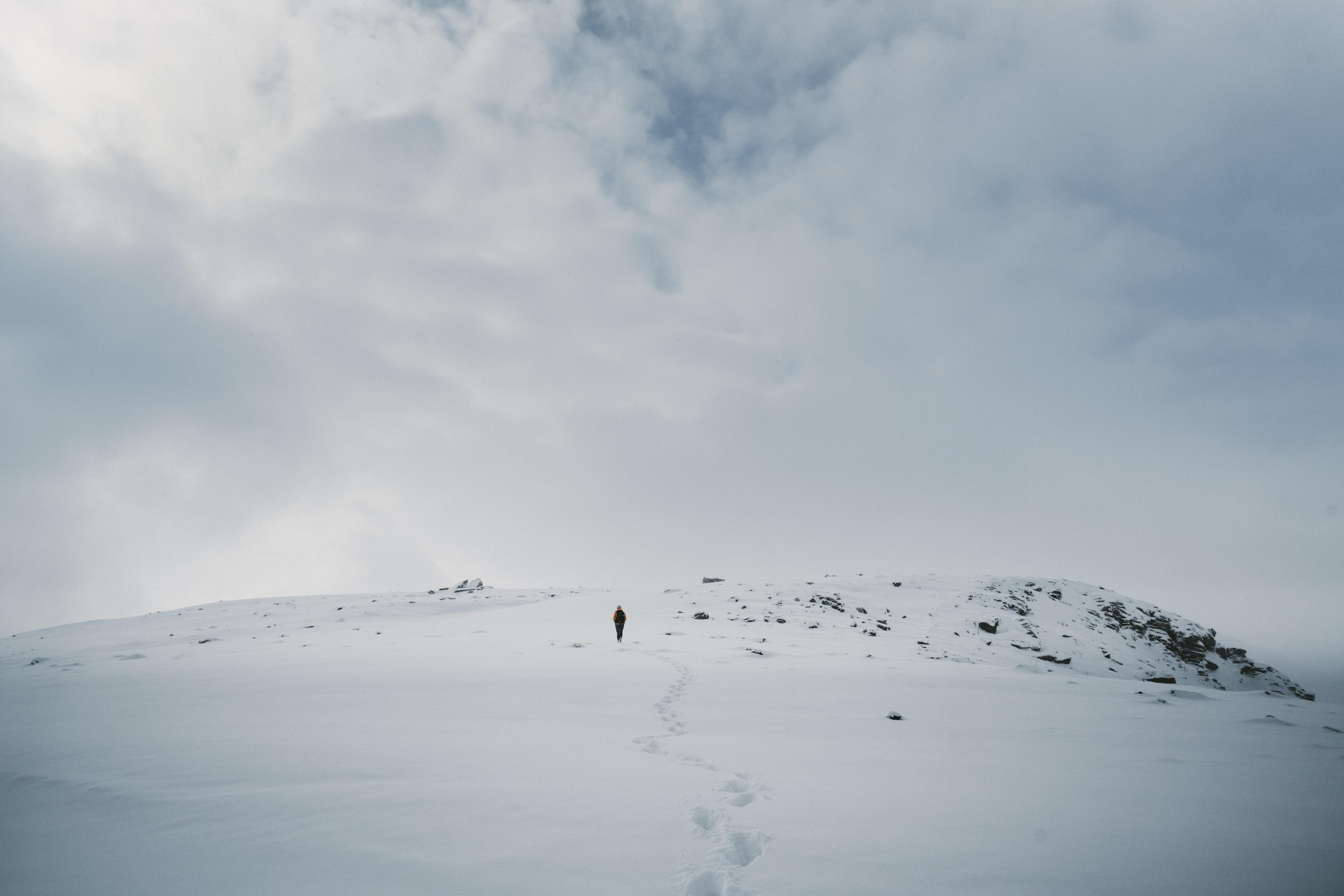 person walking on mountain during winter season