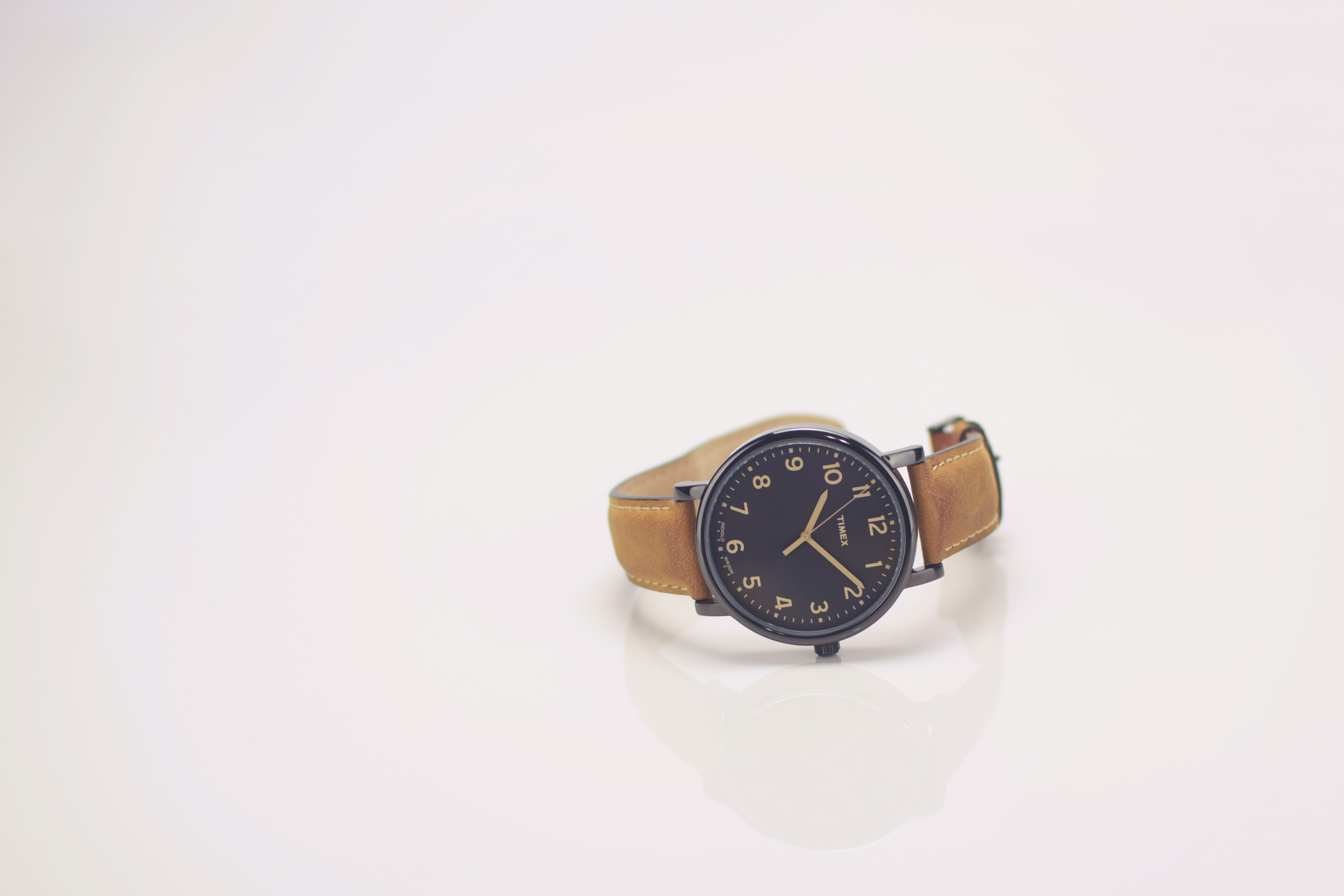 round black analog watch with brown leather band reading at 10:10