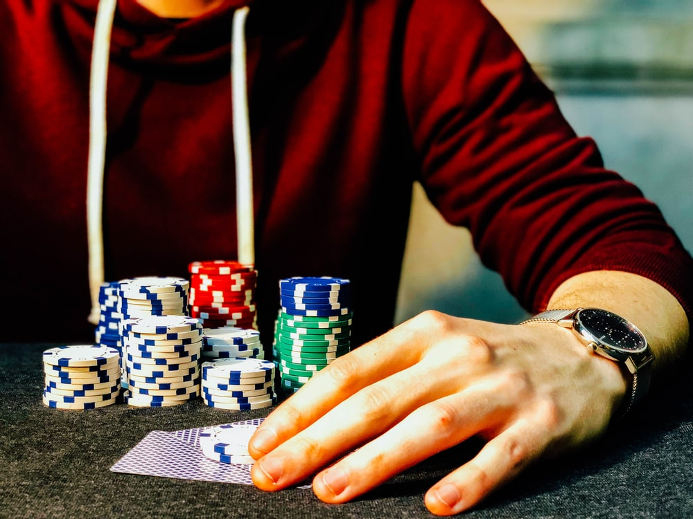 person holding playing cards beside poker chips