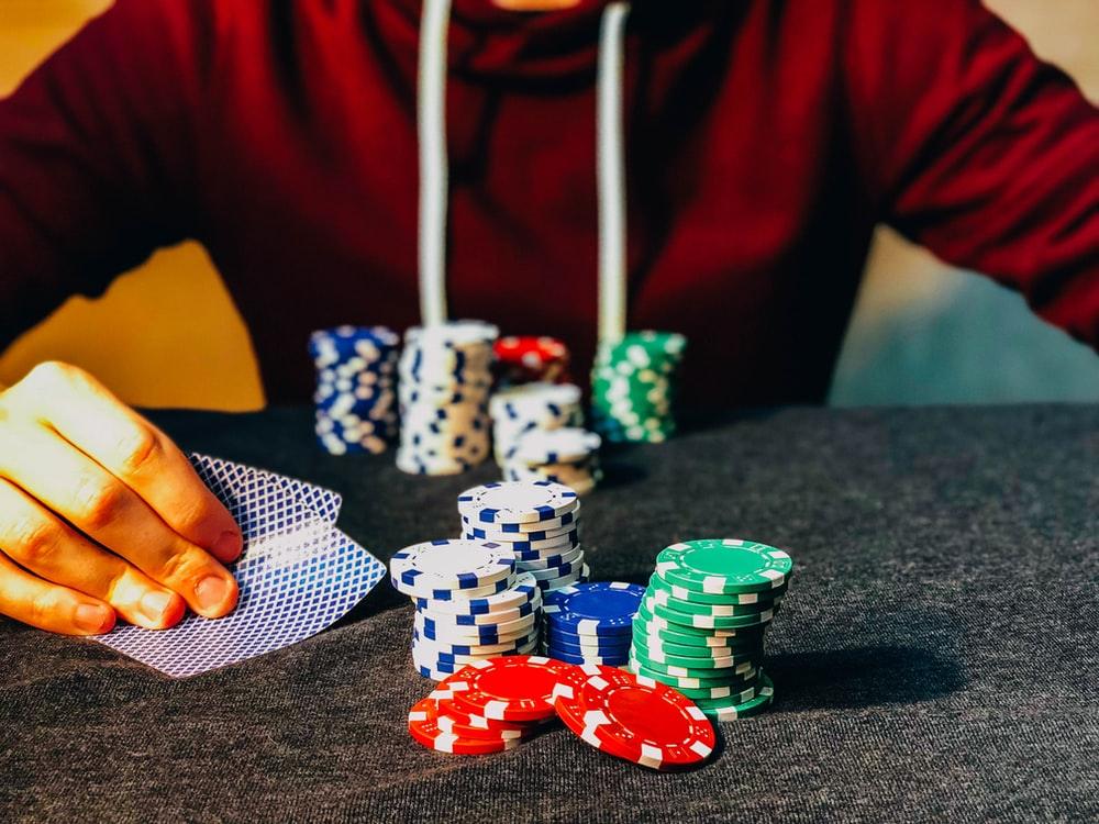 person sitting near poker chips