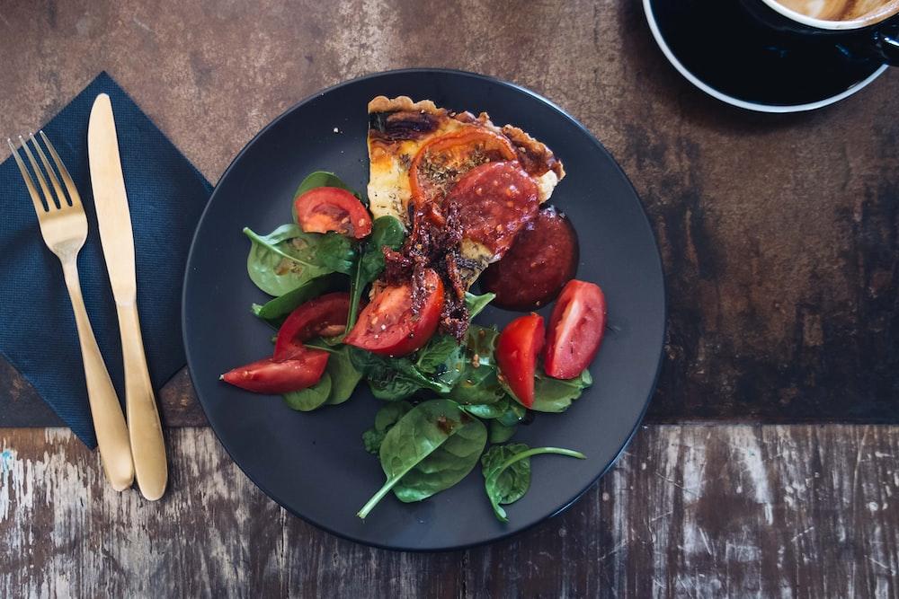 sliced tomato dish on black plate