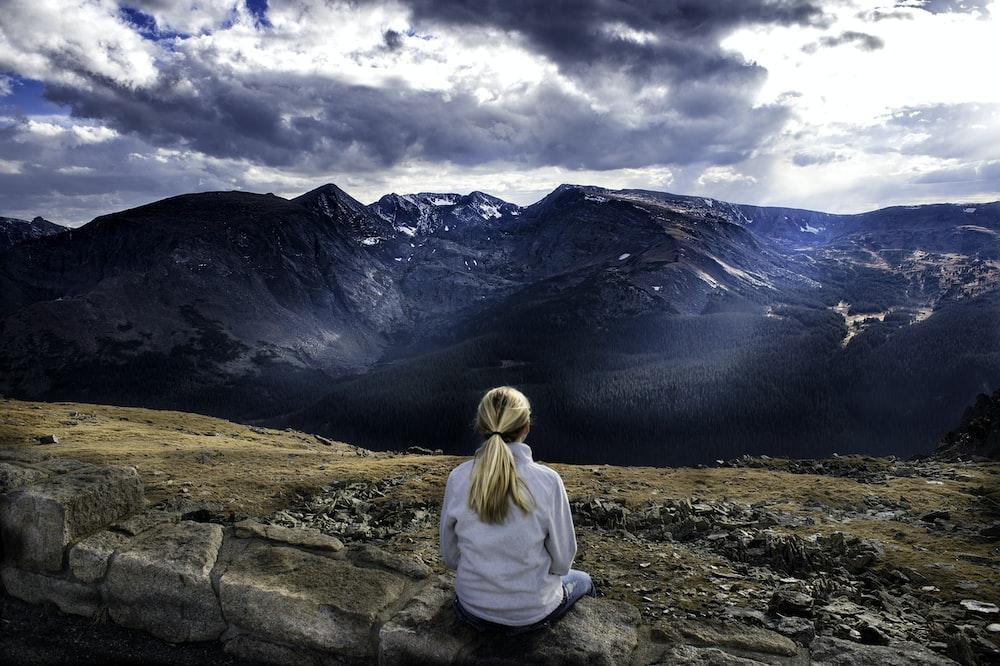 woman sitting on gray stone