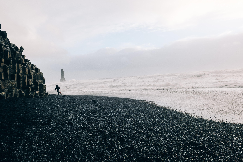 black sand shoreline under cloudy sky