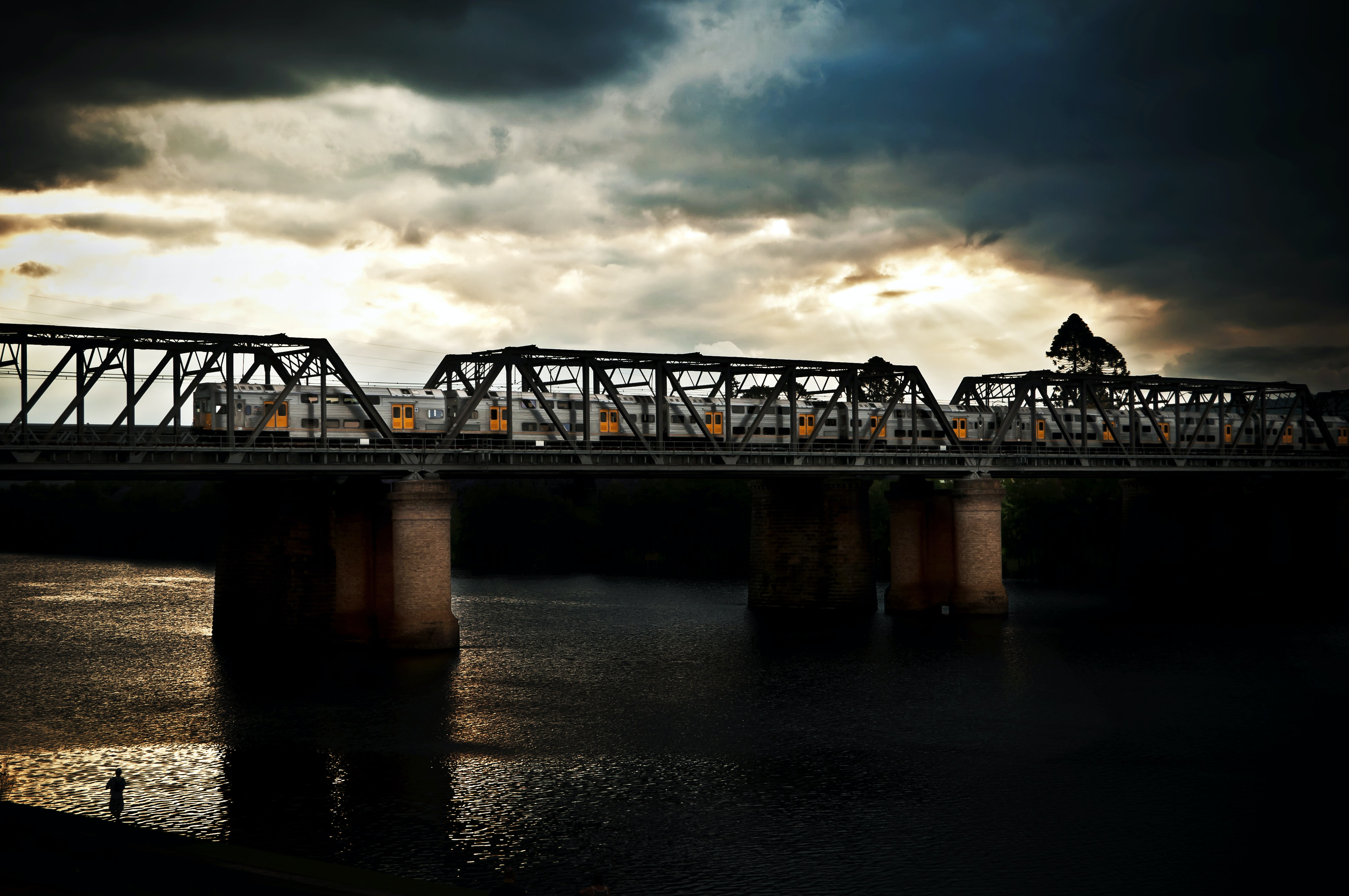 silhouette photography of bridge under nimbus clouds