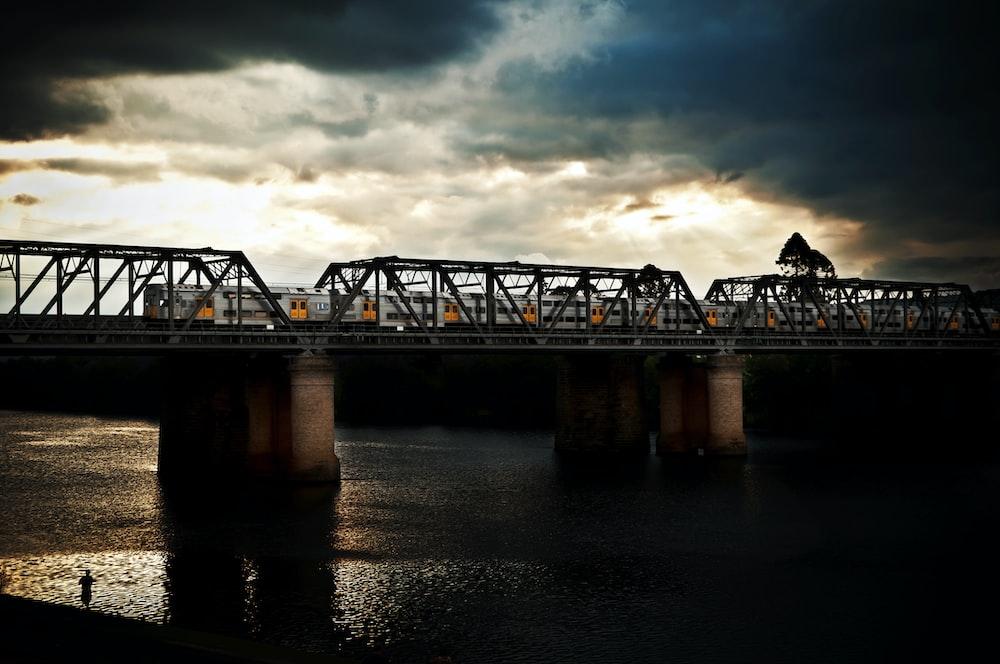 silhouette photography of bridge under nimbus clouds