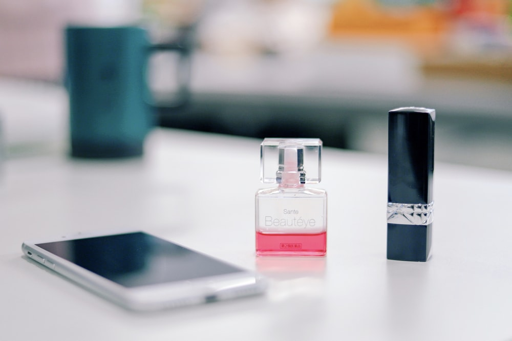smartphone on a table next to fragrance bottle and black lipstick bottle \