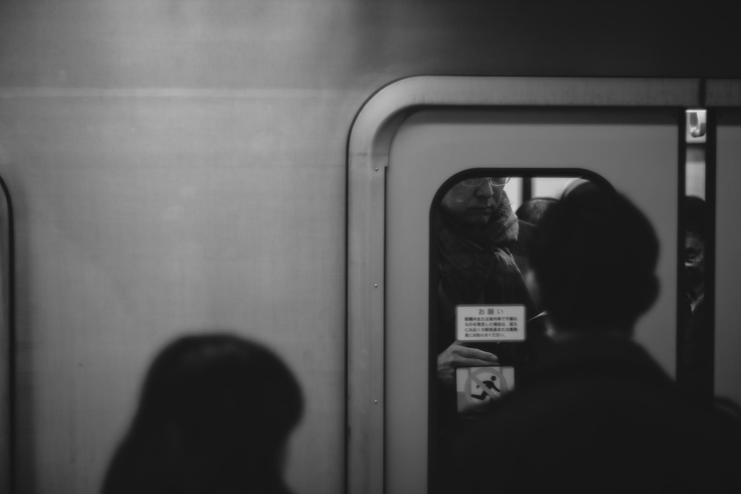 person standing on train door
