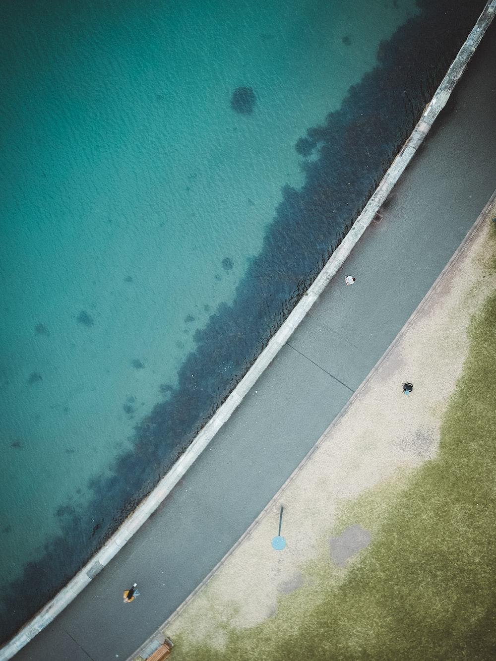 aerial view of asphalt road beside body of water