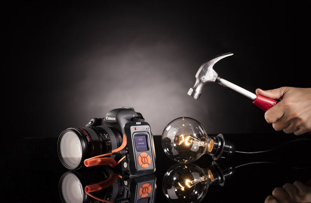 person holding claw hammer beside bulb and DSLR camera