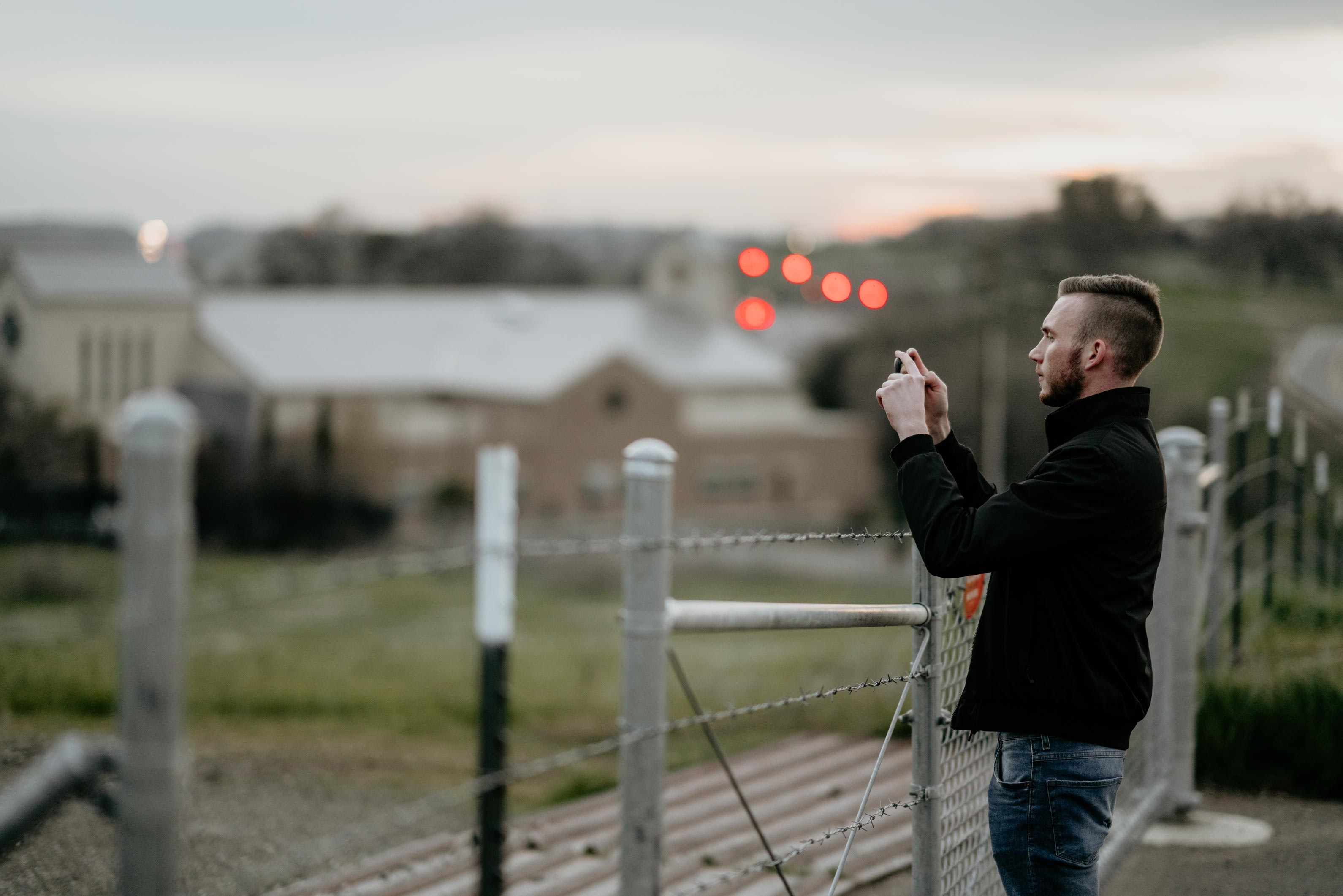 shallow focus photography of man taking a photo near fences