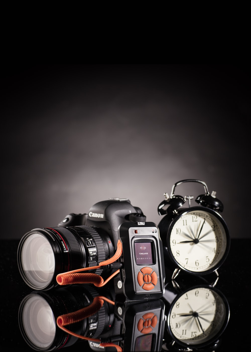 photo of Canon DSLR camera beside black twin bell alarm clock