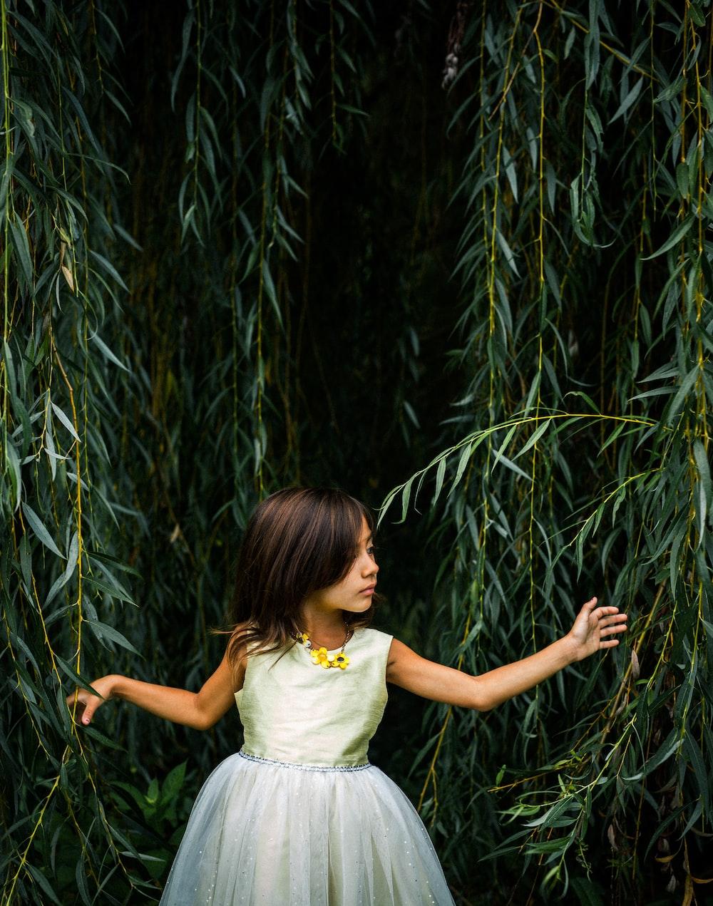 girl wearing dress standing near plants