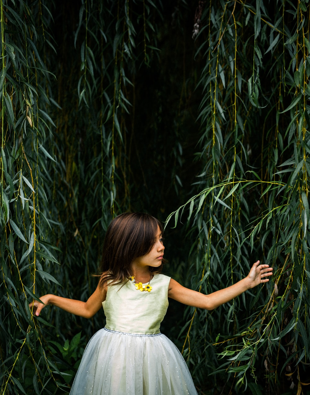 girl wearing dress standing near plants