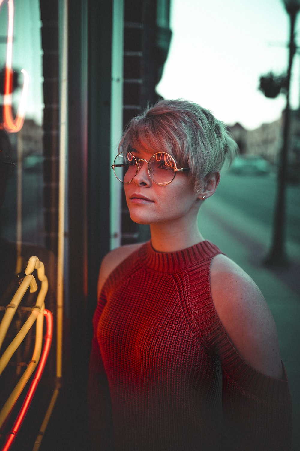 woman with eyeglasses looking at glass panel with neon signage