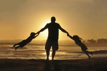 father holdings hands with kids