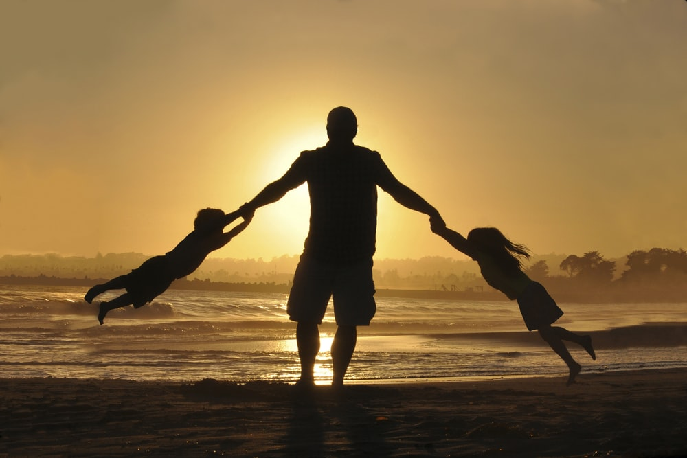 silhouette of man holding two childrens on shore during daytime