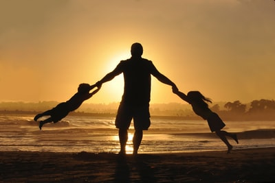 silhouette of man holding two childrens on shore during daytime day zoom background