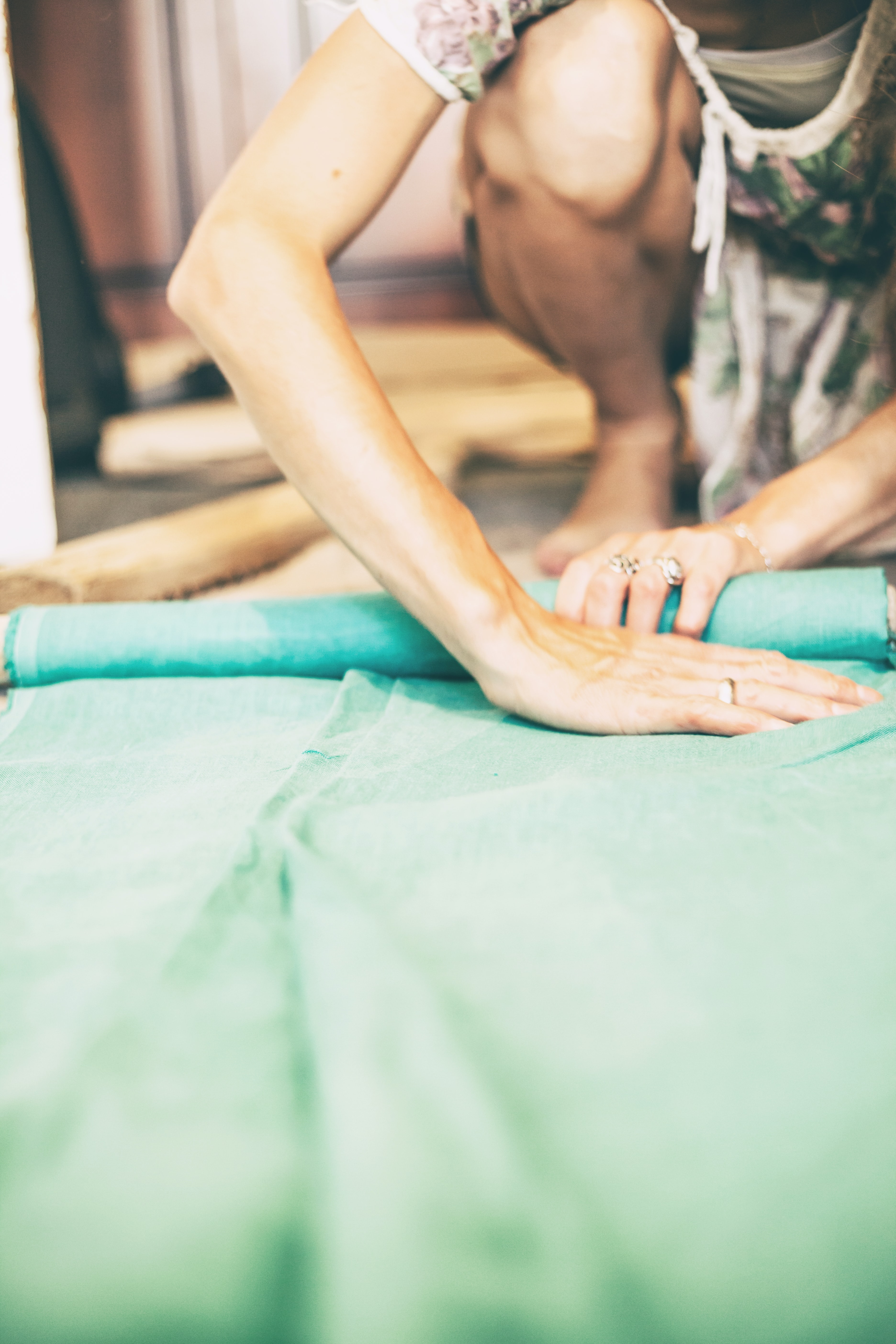 person folding green textile