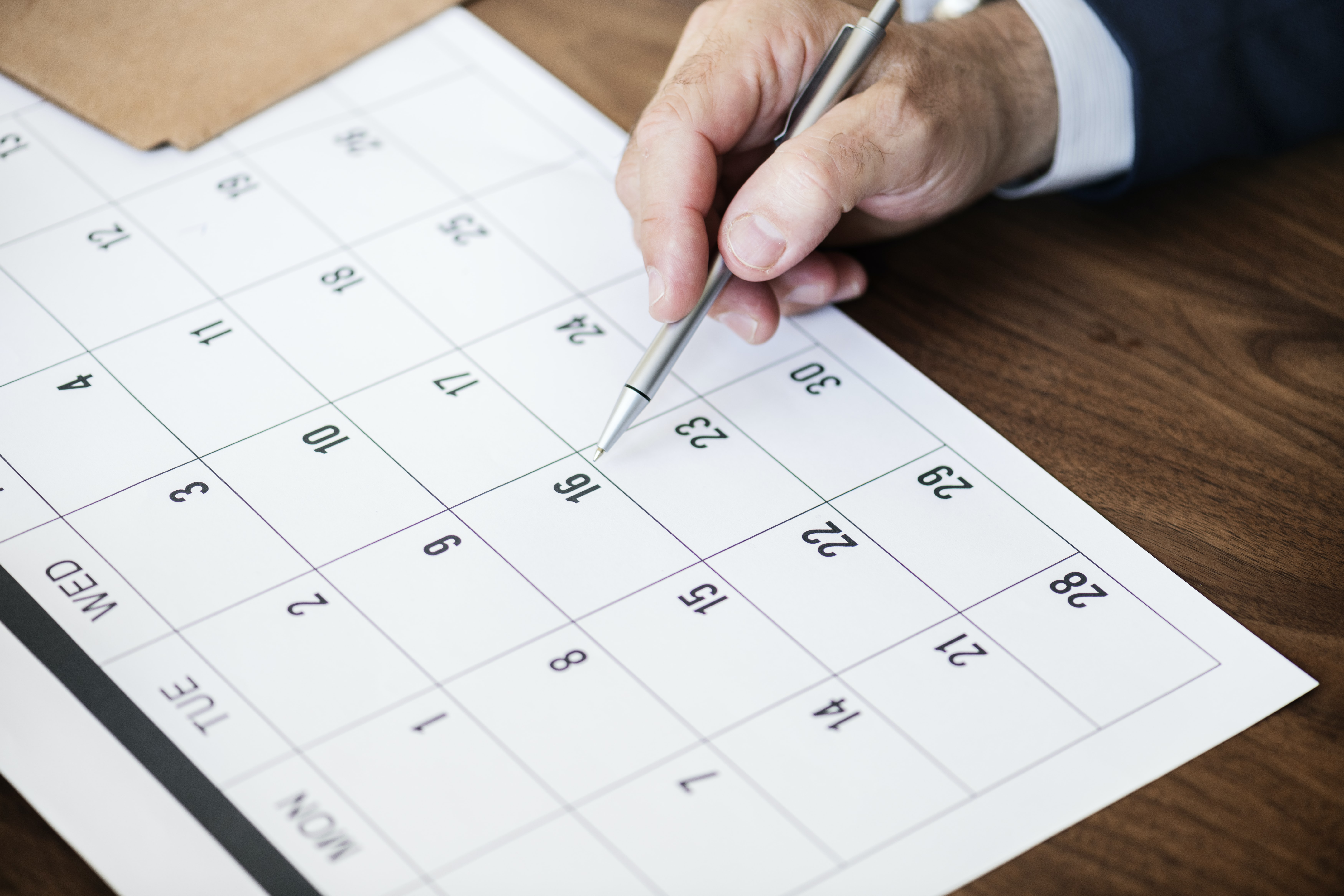 man holding pen pointing on calendar
