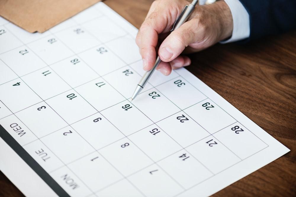 man holding pen pointing on calendar