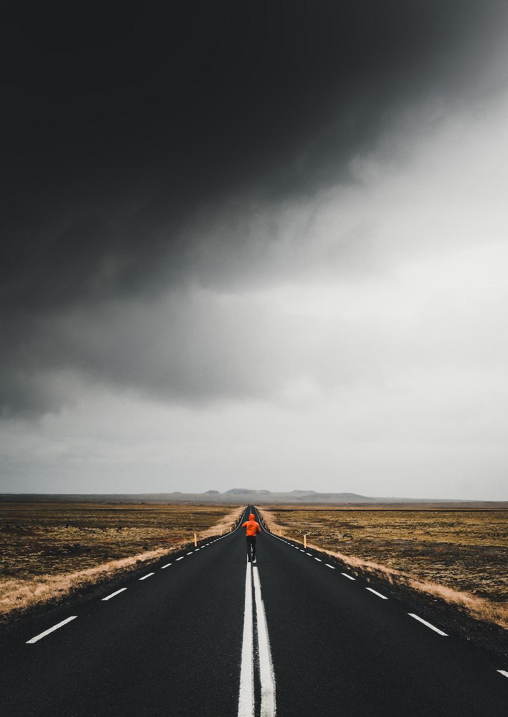 man under blacktop road under cloudy skies