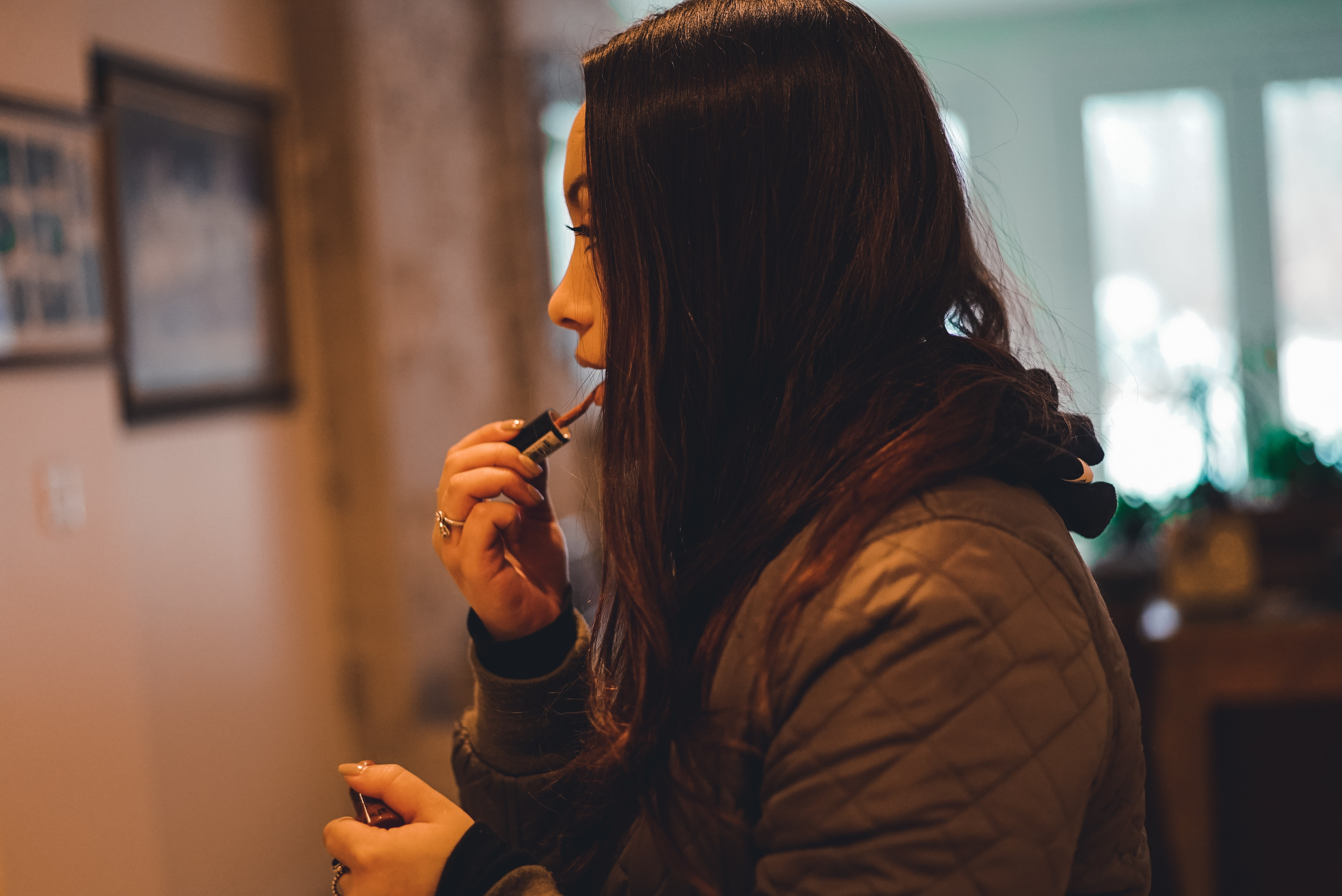 woman in brown quilted hoodie holding lipstick shallow focus photography
