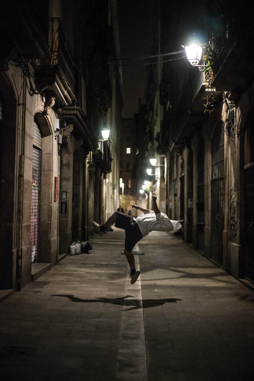 man doing acrobat trick on street