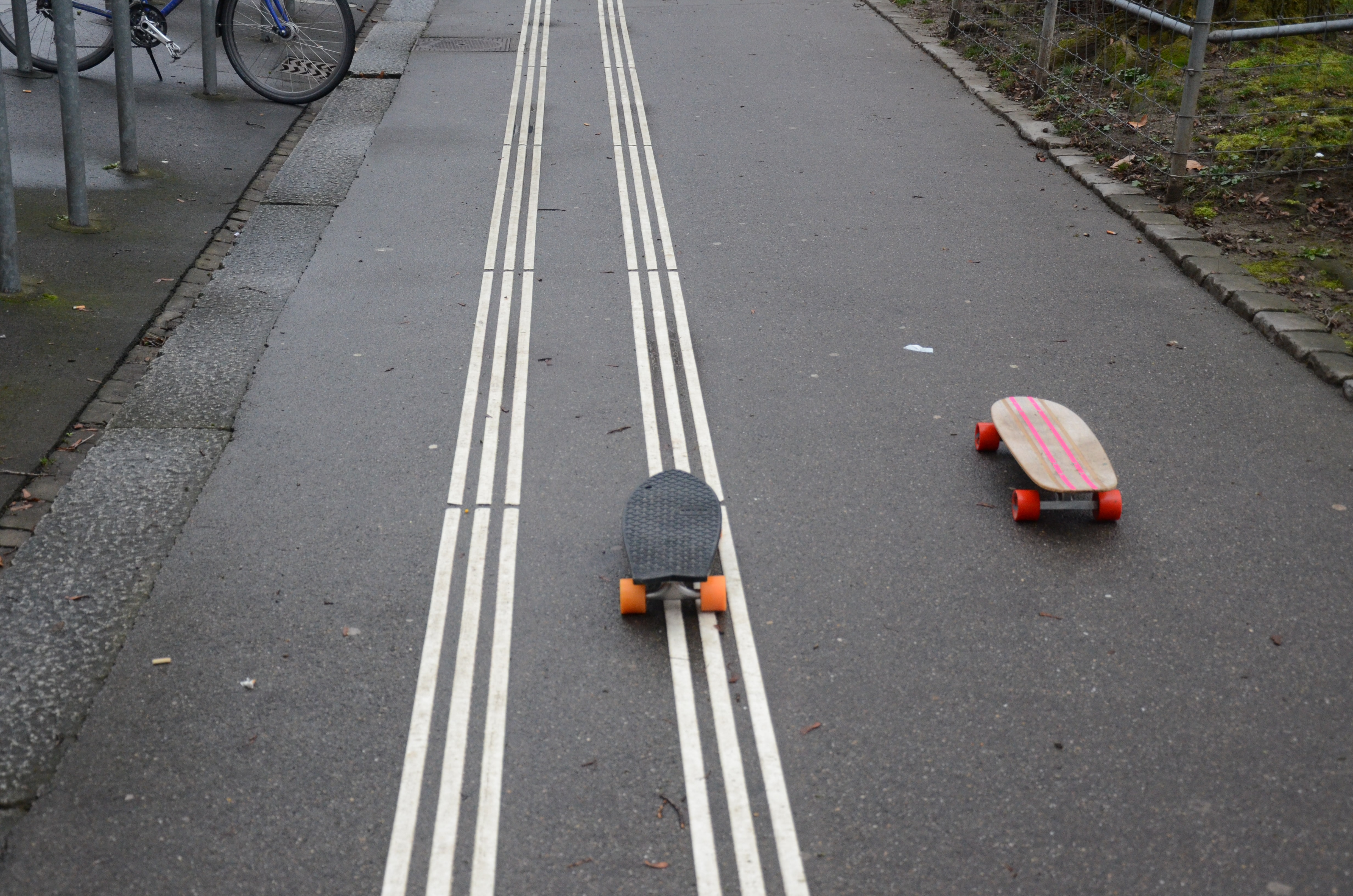 two black and brown cruiser boards on gray top road