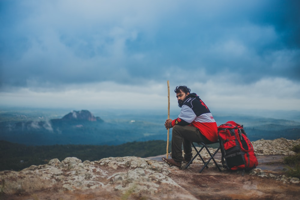 man sitting on camping chair while holding brown stick near mountain at daytime