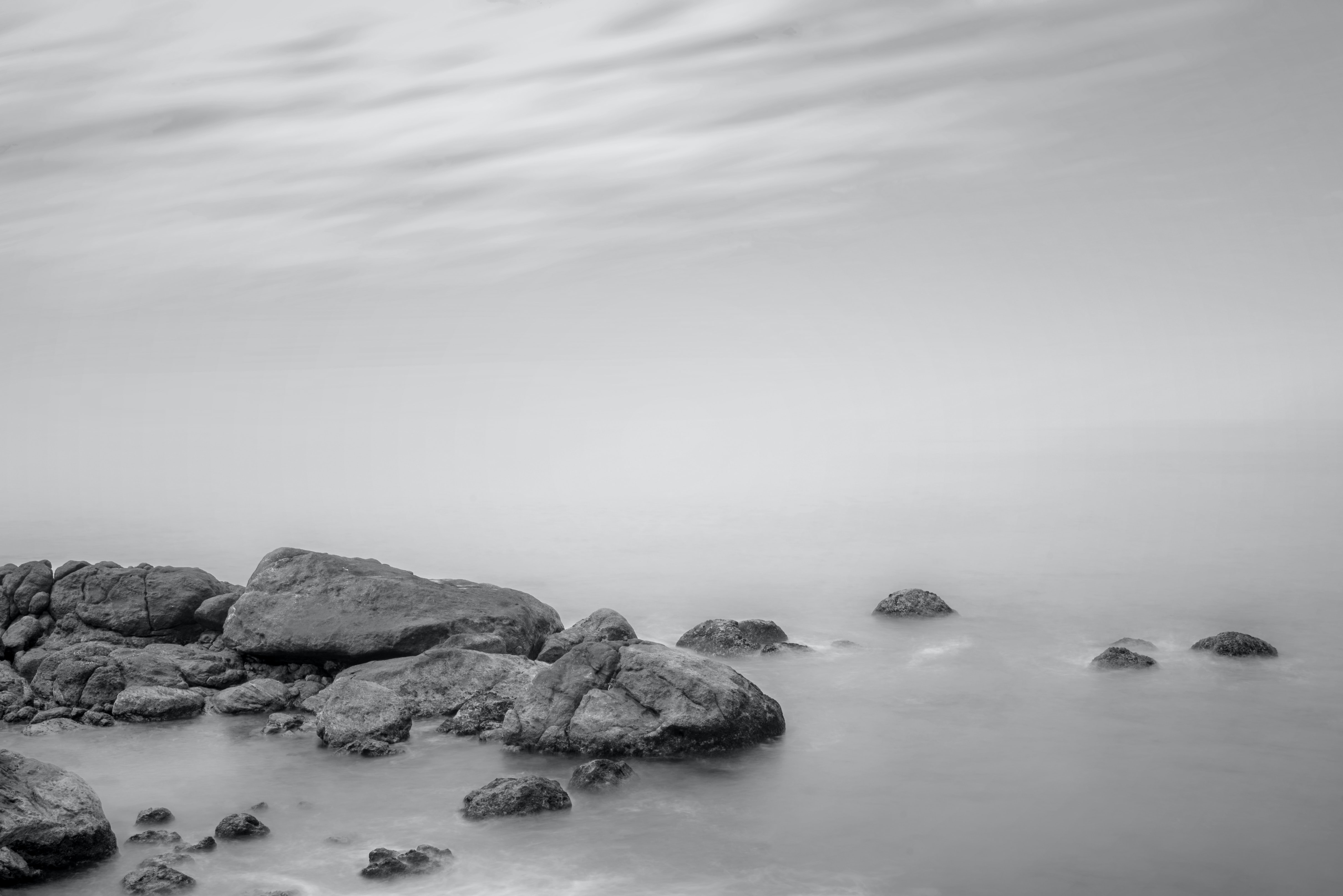 rocks beside body of water grayscale photography