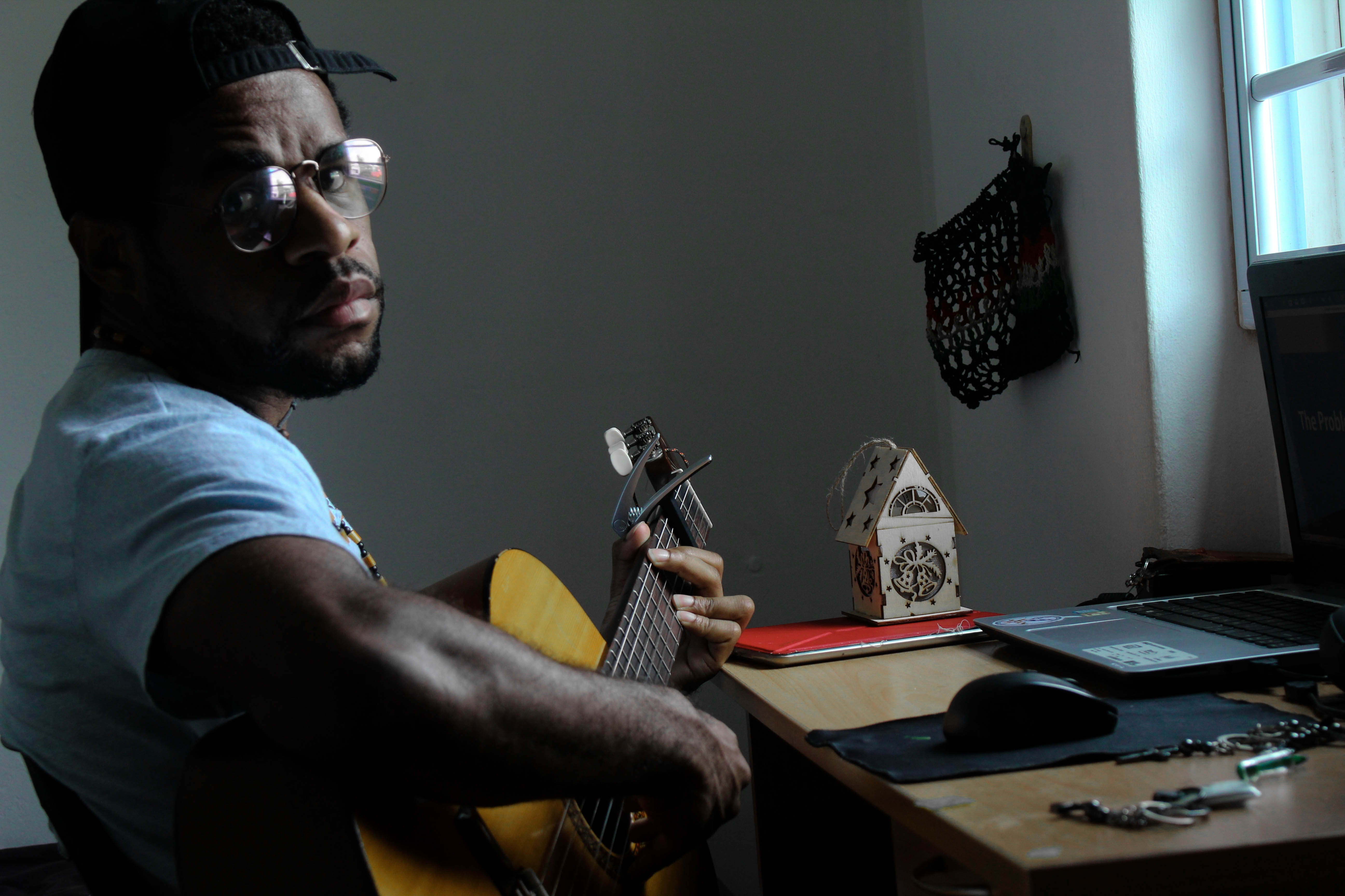 man playing guitar beside table