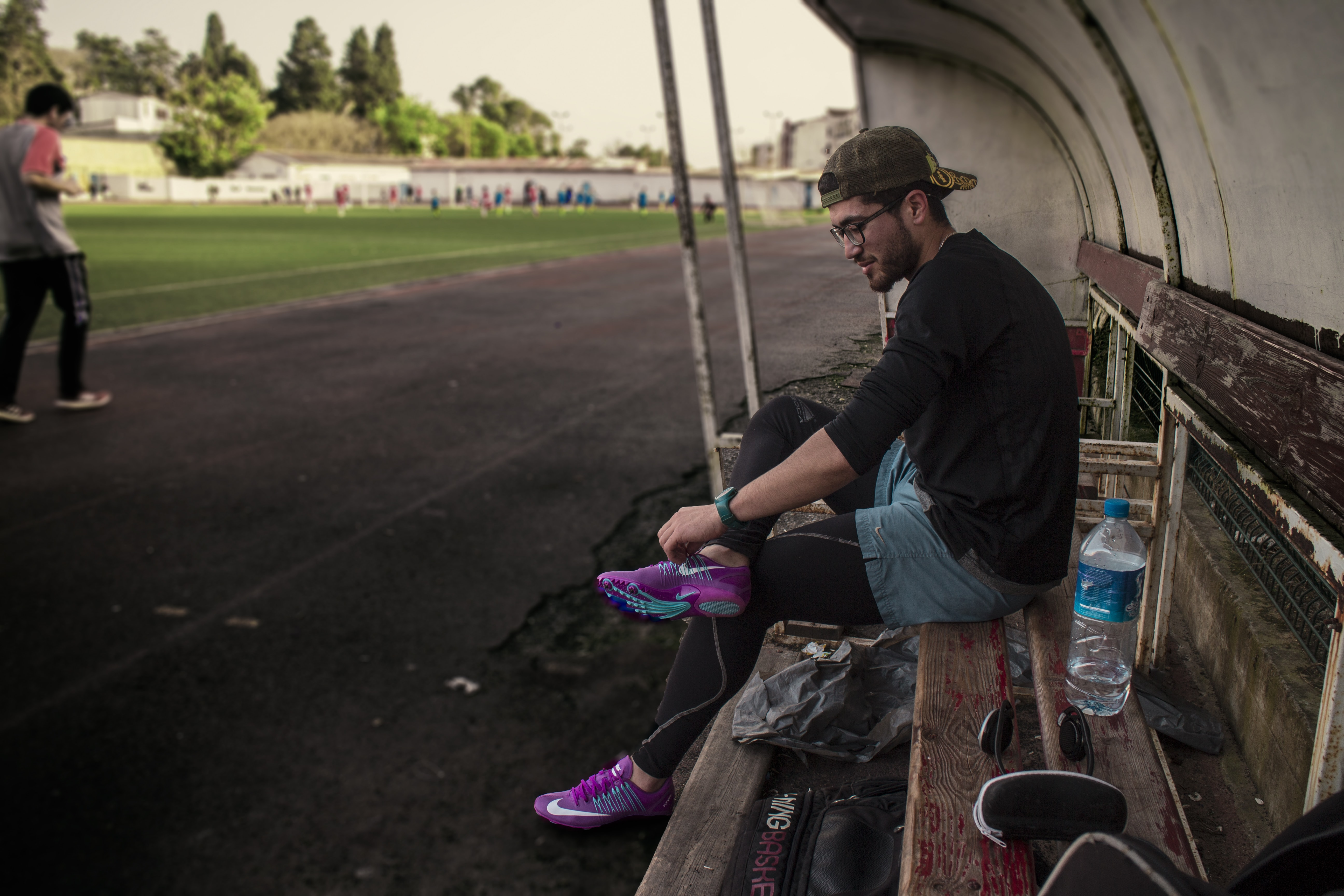 man tying his shoes while sitting on bench