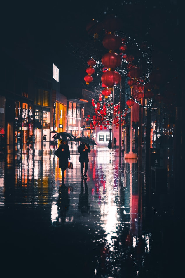 Photo of a dark city street at night where it's raining. Two people are walking with umbrellas. There are red paper lanterns in the foreground.