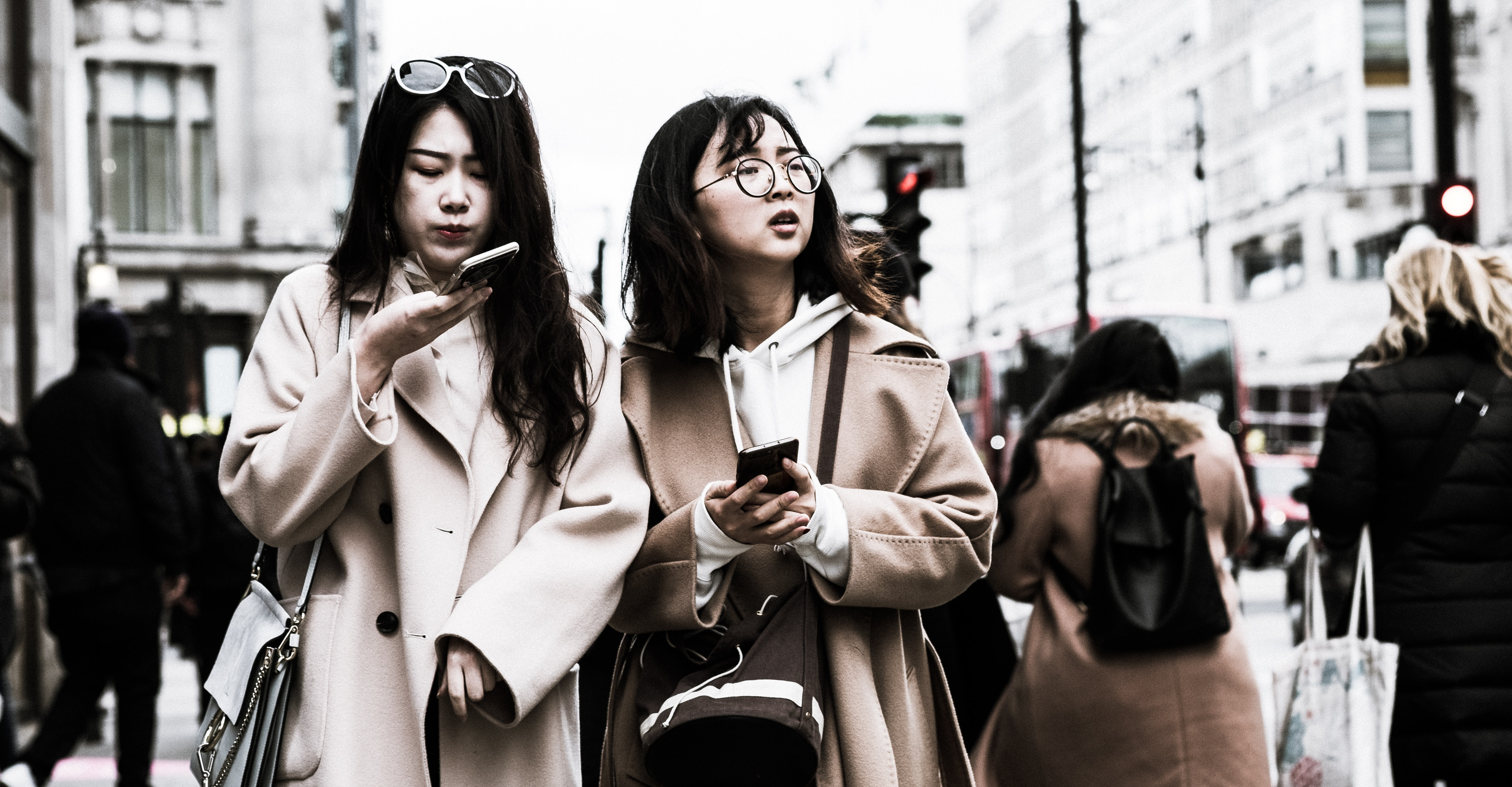 two woman holding smartphones