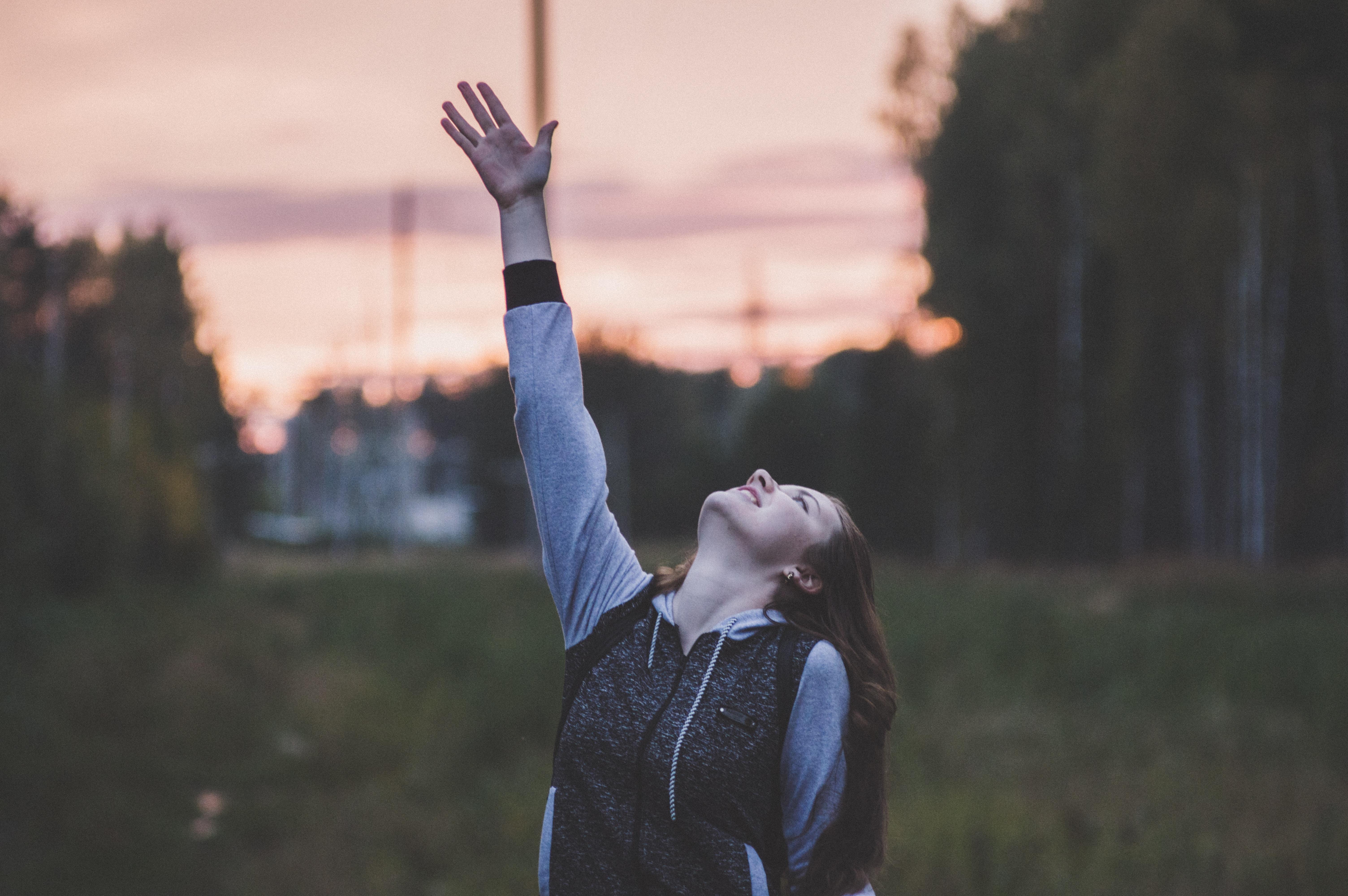 woman raising her hand outdoor