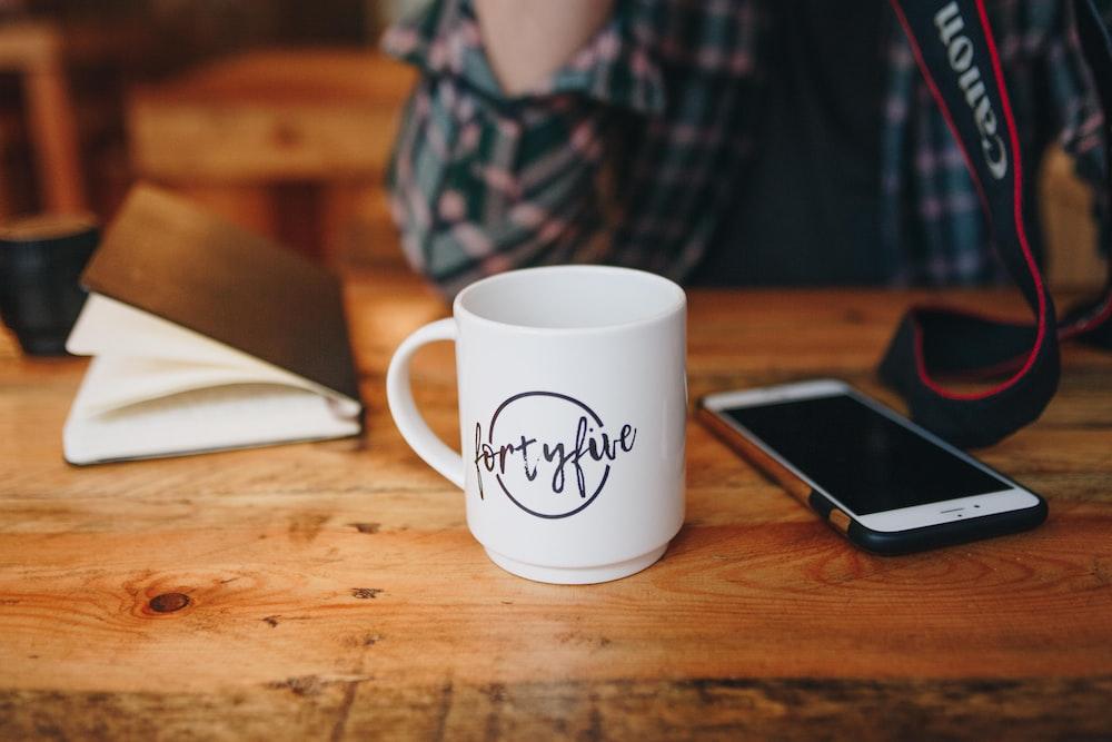 ceramic mug beside a phone on table
