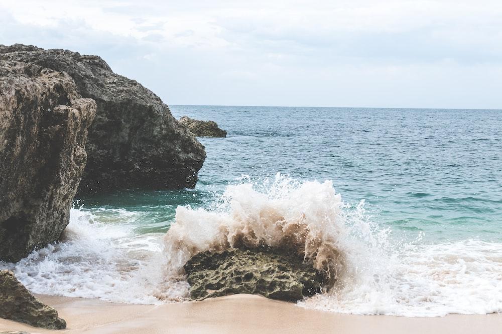 waves splashing on rock under white sky