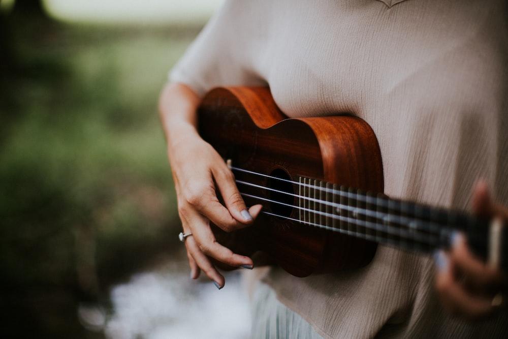 woman playing ukulele at daytime