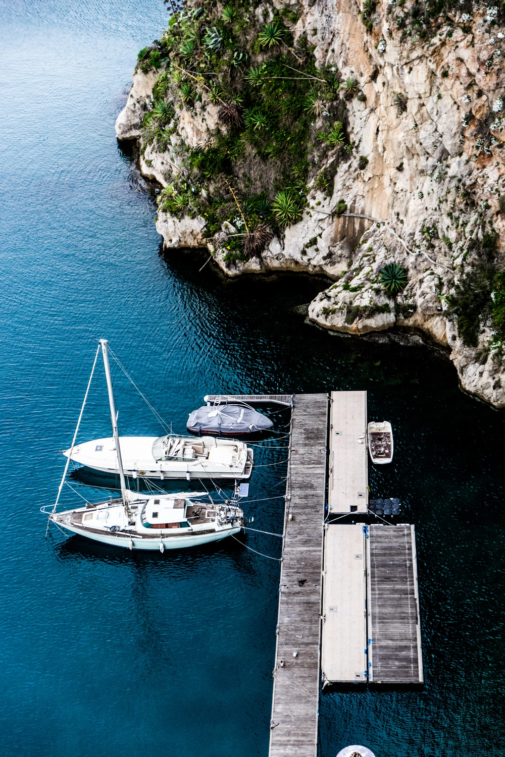 aerial photography of three yachts docking on wooden dock beside island