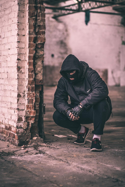 man sitting near brick wall