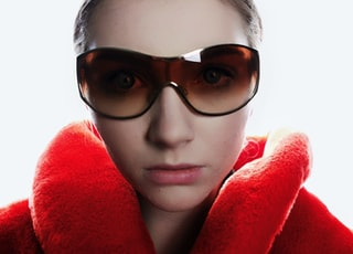woman in red coat wearing brown sunglasses