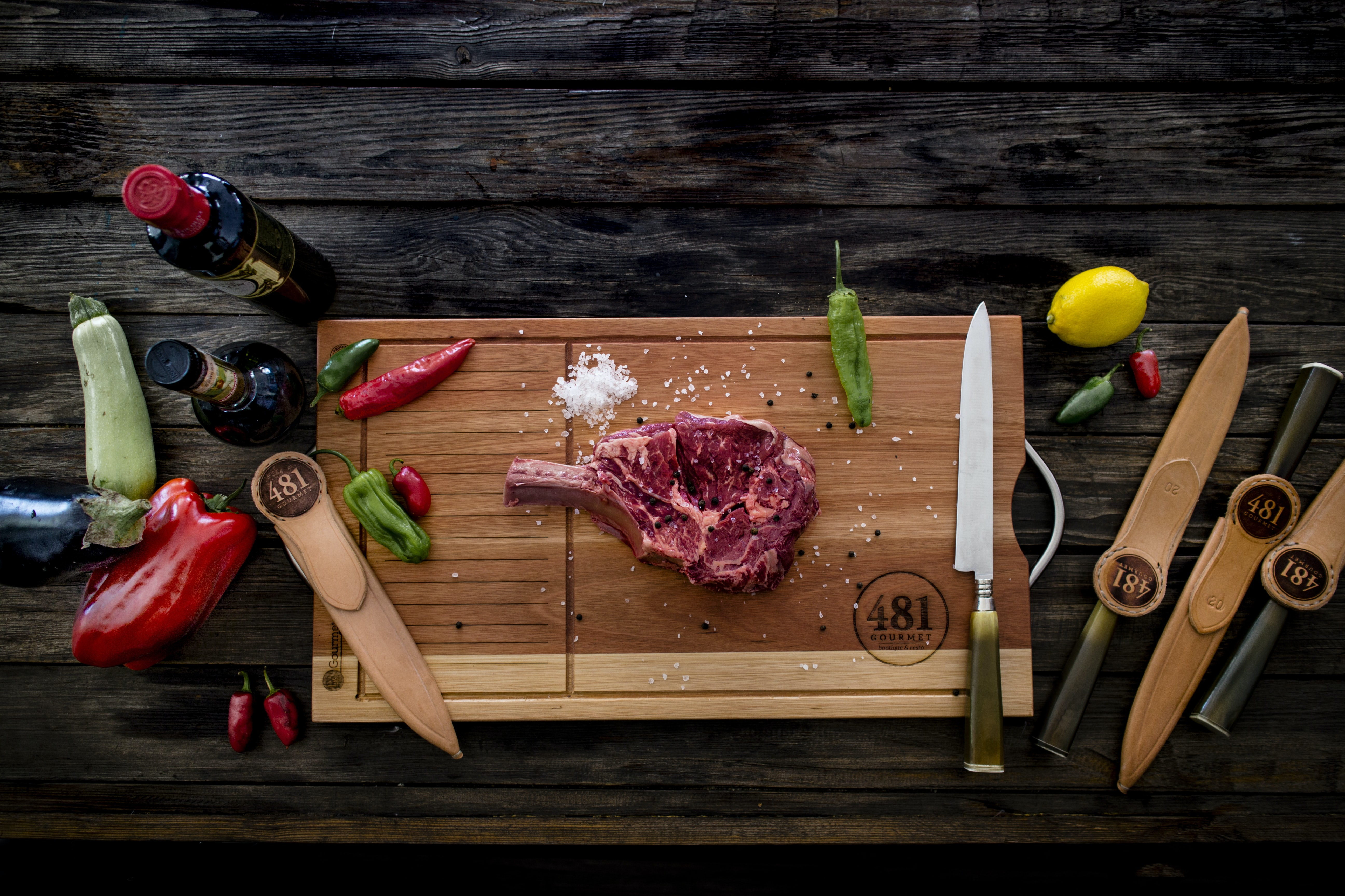 raw meat with spices on chopping board near knives