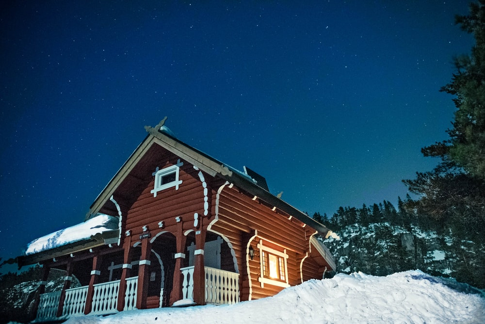low angle photography of wooden house surrounded with snow