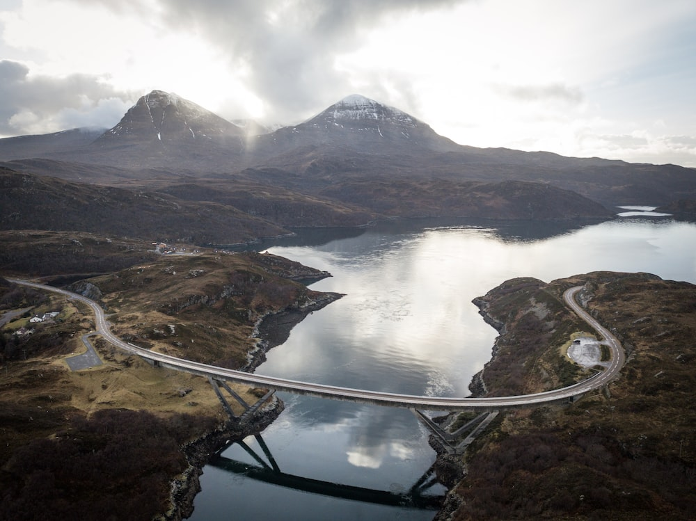 concrete road bridge near two snow-capped mountains during daytime