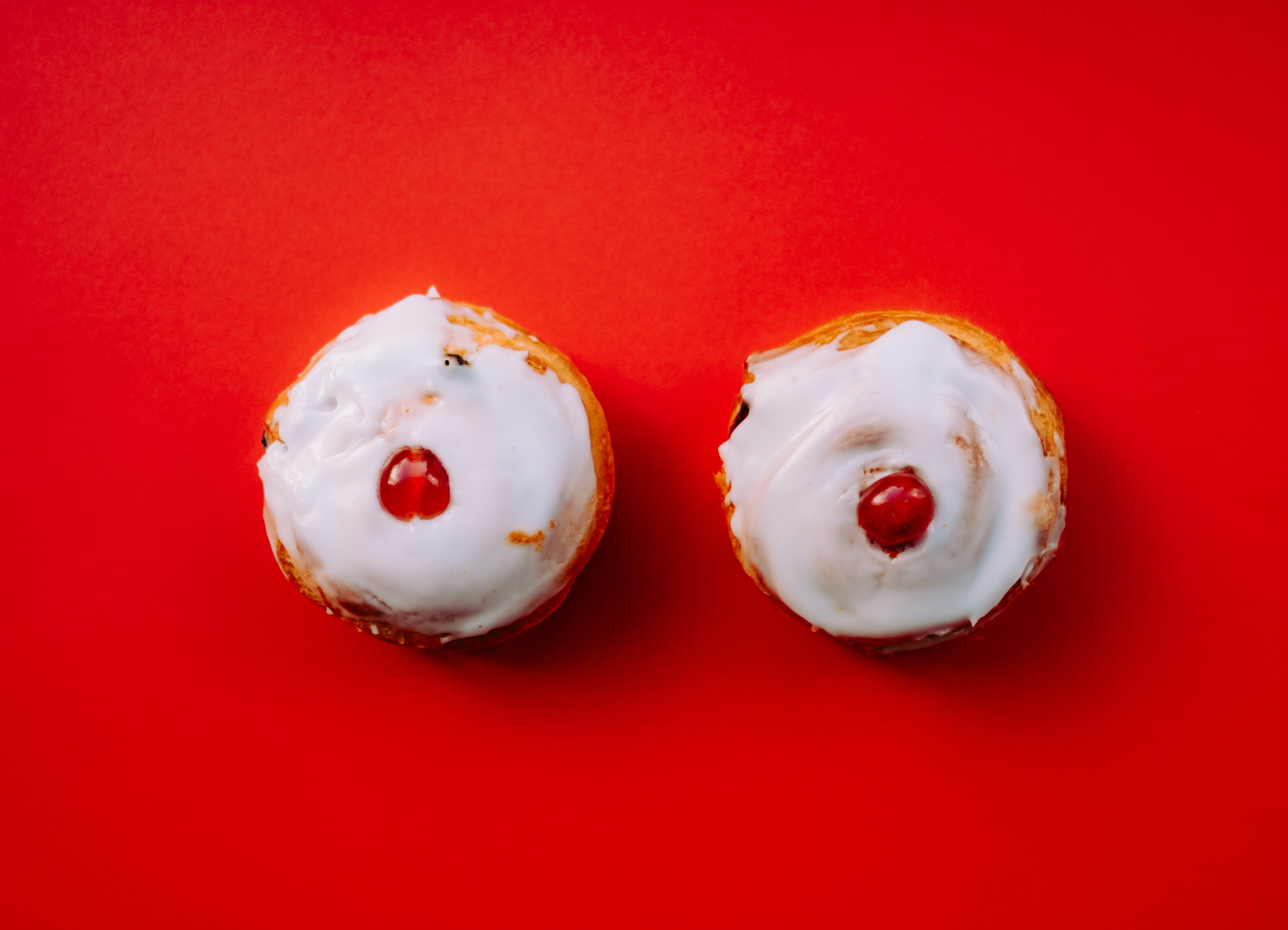 two white frosted cupcakes with cherry toppings