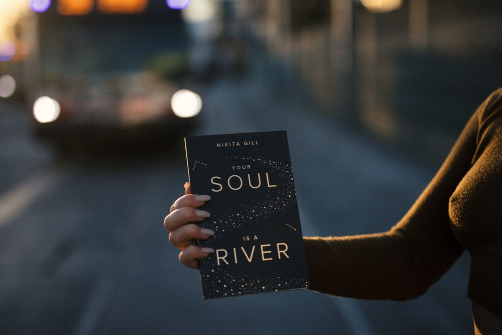 person holding Your Soul is a River book