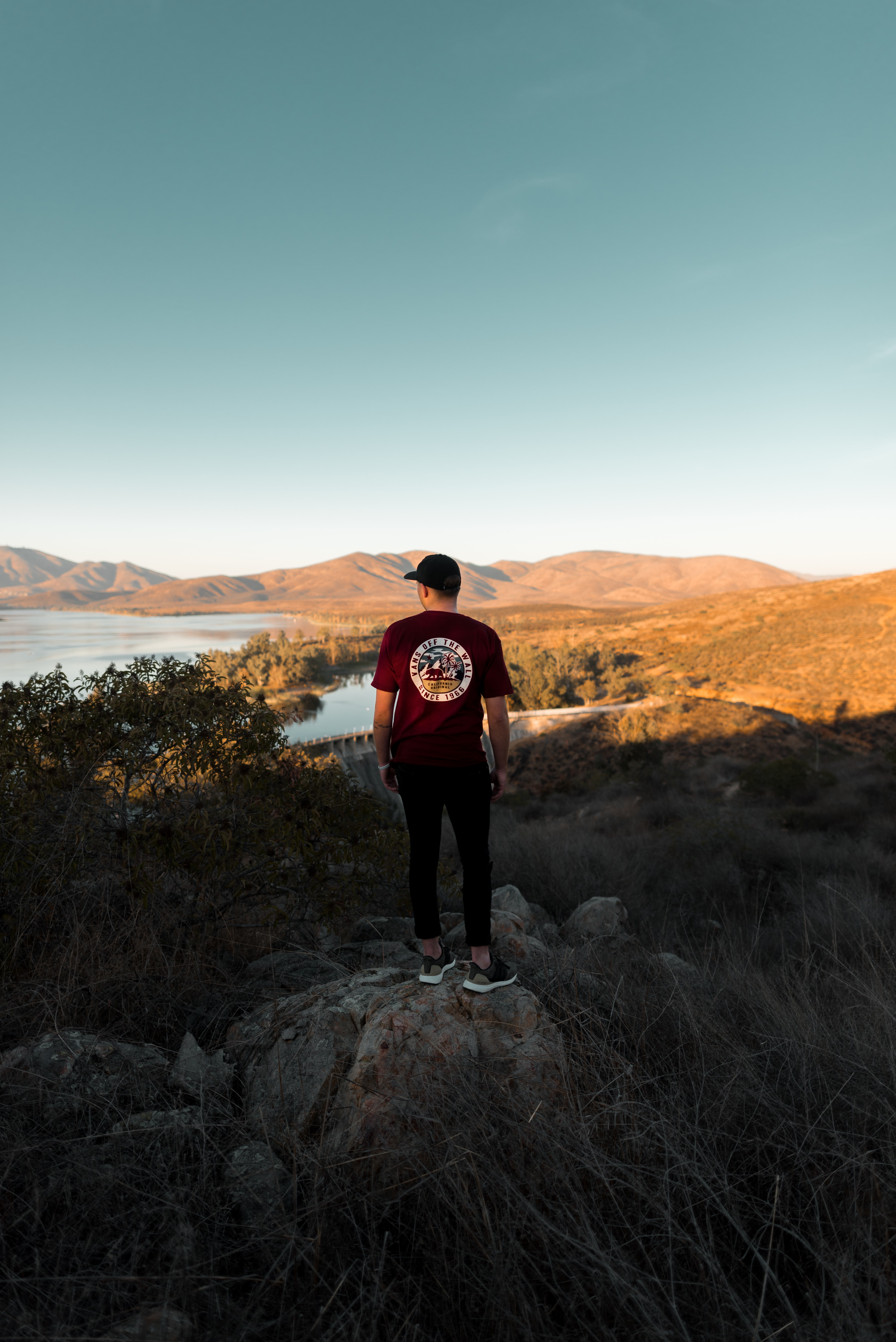 man standing on rock while watching landscapes