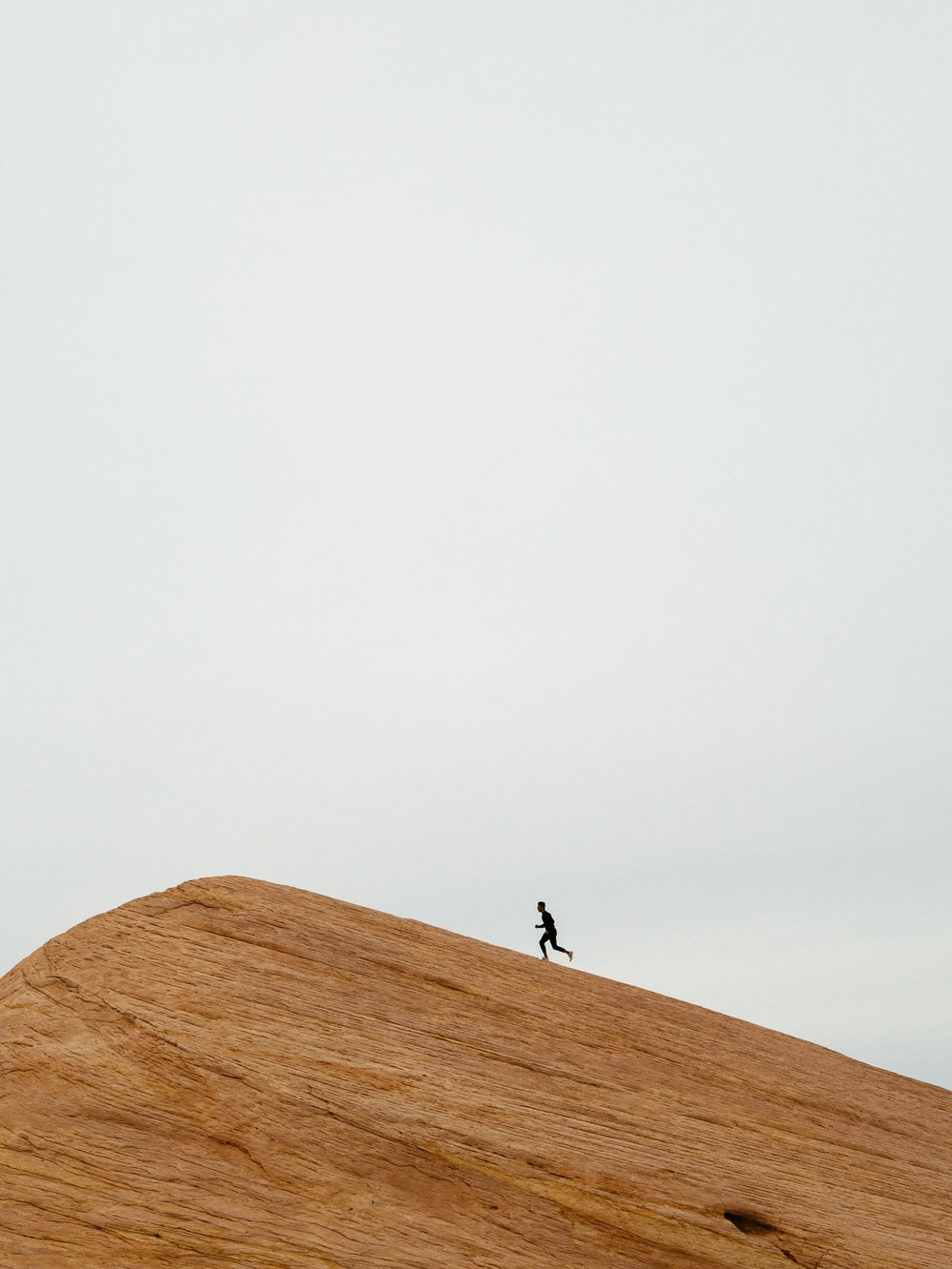 person running on top on hill during daytime