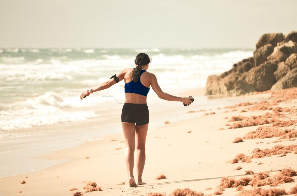 woman walking on sand near seashore during daytime