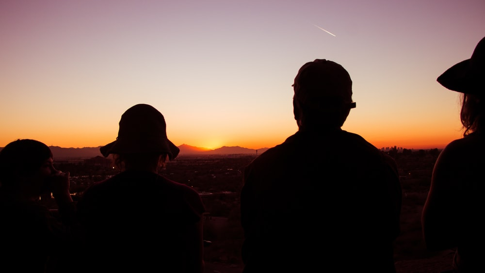 silhouette of four standing people during golden hour